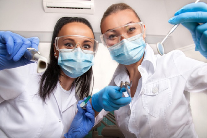 Female doctor dentist and her assistant in masks and white uniforms holding in their hands dental mirror, probe and other equipment, looking at camera and smiling